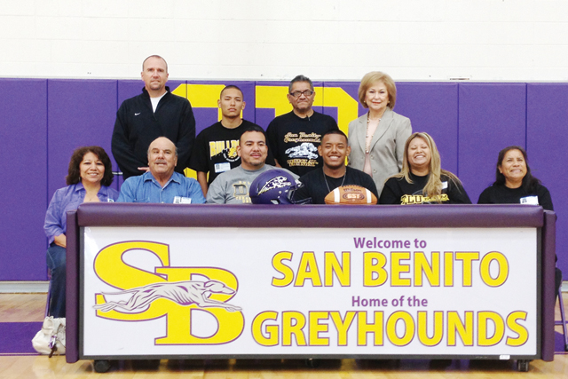 San Benito High School senior Enrique Rodriguez, a three-year varsity starter for the Greyhounds football team, is seen Thursday surrounded by his family, campus faculty and football coaches signing a letter of intent to play for Texas Lutheran University. (Staff photos by Francisco E. Jimenez)