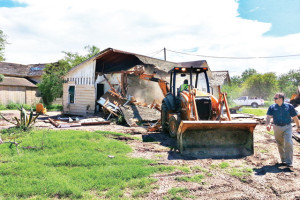 Photo by Rodrigo Davila City of San Benito employees are seen demolishing a dilapidated home on the 200 block of East Robertson Street Thursday. Shown (far right) supervising the demolition is Code Enforcement Director John Rodriguez.