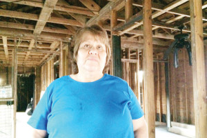(Staff photo by Michael Rodriguez) Rosie Cavazos is seen Friday morning inside the remains of her Franklin Street home, which suffered extensive fire damage in January.