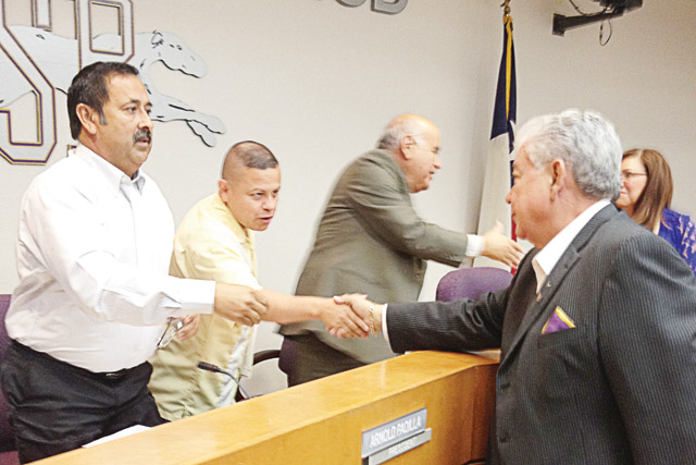 (Staff photo by Francisco E. Jimenez) San Benito CISD Superintendent of Schools Antonio G. Limón is seen Monday shaking hands with members of the SBCISD Board of Trustees, Oscar Medrano and Arnold Padilla, after he was reinstated following a year-long suspension and investigation.