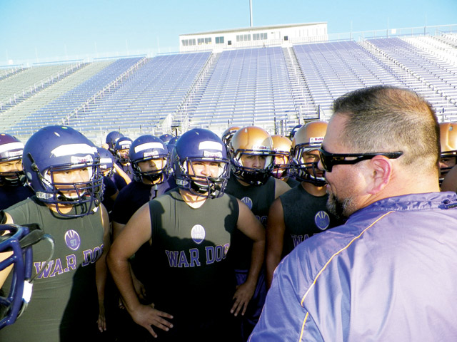 (Photo by Mathew Zuniga) Members of the San Benito Greyhound varsity football squad are seen during practice at Bobby Morrow Stadium on Tuesday receiving instruction from first-year head coach Dan Gomez.