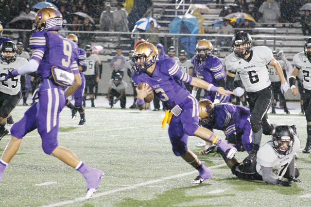 (Photo by Edward Cruz) Quarterback Cristian Sierra of the San Benito Greyhounds is seen evading Brownsville Rivera tacklers at Bobby Morrow Stadium during Friday night's District 32-6A title tilt. The 'Hounds fell to Rivera, 42-35, and are now tied for first place.